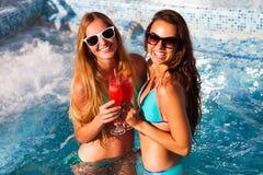 Amie heureuse avec une boisson sur une partie d'été par la piscine Photographie stock