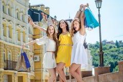 Amie heureuse de shopaholics Trois amies tenant des achats Images stock