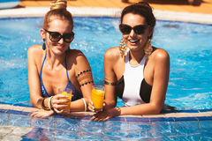 Amie heureux avec des boissons par la piscine Photo libre de droits