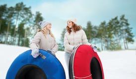 Amie heureux avec des tubes de neige dehors Photographie stock