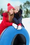 Amie heureux avec des tubes de neige dehors Image stock