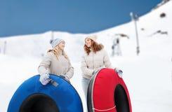 Amie heureux avec des tubes de neige dehors Photographie stock libre de droits