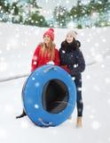 Amie heureux avec des tubes de neige dehors Images stock