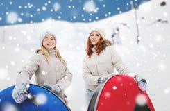 Amie heureux avec des tubes de neige dehors Image libre de droits