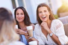Amie heureux en café pendant l'heure d'été Images stock