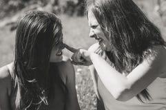 Amie heureux jouant dans l'herbe Noir et Photo libre de droits