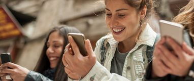 Amie heureux observant le media social d'Internet dans le téléphone portable Image libre de droits
