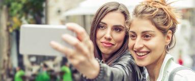 Amie heureux prenant des photos de selfie dans la rue Images stock