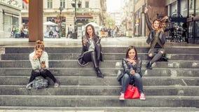 Amie heureux s'asseyant sur les escaliers de ville avec le smartphone Photo libre de droits