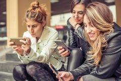 Amie heureux s'asseyant sur les escaliers de ville avec le smartphone Photographie stock