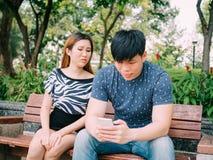 Amie jalouse jetant un coup d'oeil et remarquant son téléphone portable d'ami Images libres de droits