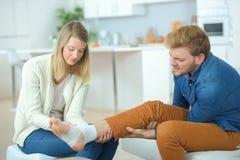 Amie mettant le bandage sur la jambe Image stock