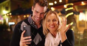 Amie millénaire prenant des selfies avec sa nouvelle bague de fiançailles Photo stock