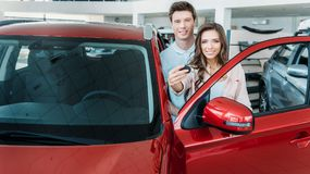 amie montrant la clé de la nouvelle voiture dans la salle d'exposition, ami Images stock