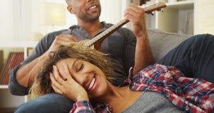 Amie noire appréciant être chanté une sérénade à par l'ami Image stock