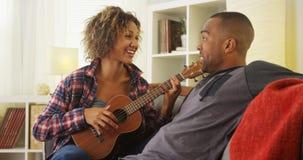 Amie noire chantant une sérénade à son ami avec l'ukulélé Photographie stock