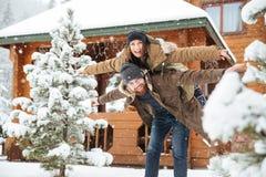 Amie piggibacking d'homme barbu gai et amusement de avoir en hiver Photographie stock libre de droits
