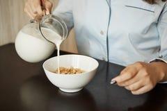 Amie préparant le petit déjeuner simple dans le matin Tir cultivé de femme en lait se renversant de chemises de nuit dans la cuve Photo libre de droits