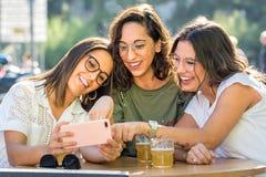Amie riants de groupe de trois personnes avec le smartphone sur la terrasse images libres de droits