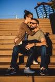 Amie s'asseyant dans son recouvrement d'ami et l'embrassant Photos libres de droits