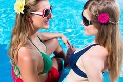 Amie se bronzant à la piscine devant l'eau Photo libre de droits