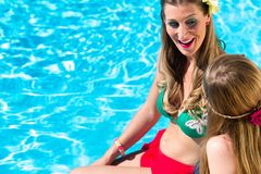 Amie se bronzant à la piscine devant l'eau Photographie stock libre de droits