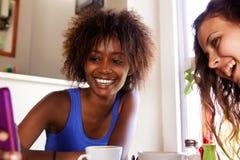 Amie souriant et regardant le téléphone portable Image stock