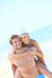 Amie sur le dos de l'ami sur la plage Photos libres de droits