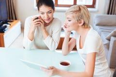 Amies à l'aide de la tablette dans la cuisine Photo stock
