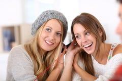 Amies écoutant la musique partageant des écouteurs Photographie stock