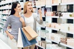 Amies élégantes avec le parfum d'achat de sacs Boutique de parfum Photo libre de droits