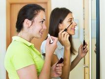 Amies adolescentes ayant l'amusement près du miroir Images stock