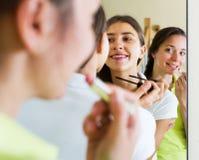 Amies adolescentes ayant l'amusement près du miroir Photographie stock libre de droits