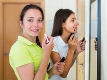 Amies adolescentes ayant l'amusement près du miroir Images libres de droits