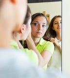Amies adolescentes ayant l'amusement près du miroir Image libre de droits