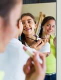 Amies adolescentes ayant l'amusement près du miroir Photographie stock
