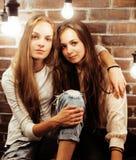 Amies assez adolescentes ayant l'amusement dans le studio moderne élégant de grenier, concept de personnes de mode de vie Photo libre de droits