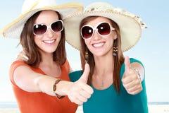 Amies attirantes pendant le jour d'été montrant le pouce  Photographie stock