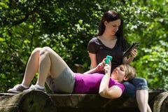 Amies au parc utilisant le smartphone et le comprimé, horizontaux Image libre de droits