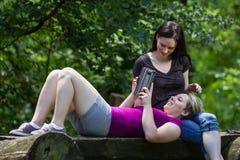 Amies au parc utilisant le smartphone et le comprimé, horizontaux Images libres de droits