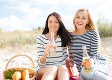 Amies avec des bouteilles de bière sur la plage Image stock
