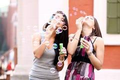 Amies avec des bulles de savon dehors Photographie stock