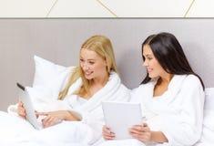 Amies avec des ordinateurs de PC de comprimé dans le lit Photos libres de droits