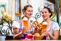 Amies avec le bretzel et la bière dans l'auberge bavaroise Photo stock