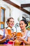 Amies avec le bretzel et la bière dans l'auberge bavaroise Photos stock