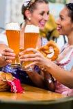 Amies avec le bretzel et la bière dans l'auberge bavaroise Images stock