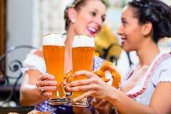 Amies avec le bretzel et la bière dans l'auberge bavaroise Photographie stock