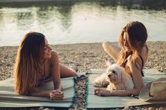 Amies avec le chien se trouvant sur la plage et le sourire Photographie stock libre de droits