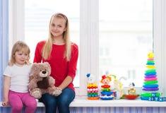 Amies avec un jouet se reposant sur le rebord de fenêtre Photos stock