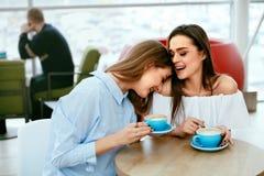 Amies buvant du café en café Image stock